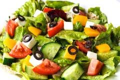 Griechischer Salat in einer Platte auf einer lokalisierten weißen Hintergrundnahaufnahme stockfotos