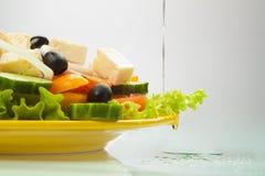 Griechischer Salat mit dem Schmierölfließen Lizenzfreie Stockfotos