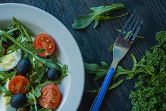 Griechischer Salat mit frischen Tomaten, Arugula, Eier, Oliven mit Oliven?l auf einem dunklen h?lzernen Hintergrund Gesunde Nahru lizenzfreie stockfotografie
