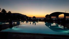 Griechischer Sonnenuntergang durch Swimmingpool lizenzfreies stockbild