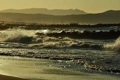 Griechischer Strand, Wellenbrecher und Hafen am Abend Stockbild