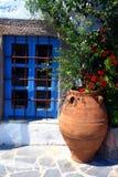 Griechisches Fenster mit eingemachten Blumen Stockfotos