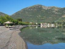 Griechisches Fischerdorf unter grünem Berg Lizenzfreies Stockfoto