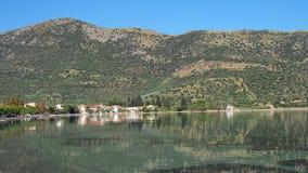 Griechisches Fischerdorf unter grünem Berg Stockfotos