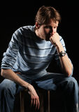 Grief. Lonely man in blue sweater sitting on chair Stock Image