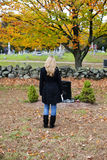Grief. A back view of a young woman standing in a cemetery Royalty Free Stock Photography
