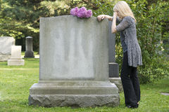 Grief in the Cemetery. Woman mourns in cemetery resting on gravestone Royalty Free Stock Photo