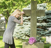 Grief and Death. Woman mourns in cemetery resting on cross gravestone stock photography