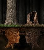Grief And Grieving. Concept as two trees with roots shaped as human heads with one dead tree in a forest as a symbol for loss and a metaphor for spirituality in Royalty Free Stock Images