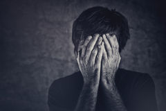 Grief, man covering fsce and crying Stock Photo