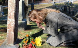 Grief-stricken lady with flowers at grave Stock Photo