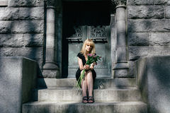 Grief:  Woman Sitting on Mausoleum Steps. Woman sitting on steps of mausoleum with flowers in cemetery for grief, loss and death concept Stock Photography