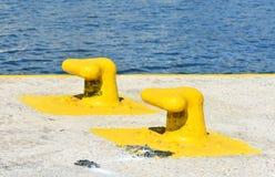 Griekenland, het Eiland Sikinos in de Cycladen Twee gele geschilderde meerpalen bij het dok royalty-vrije stock afbeeldingen