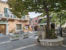 Griekenland, Korfu, Doukades, 28 september, 2018: Oud vierkant met grote lindeboom en herbergen en steen traditionele huizen royalty-vrije stock foto