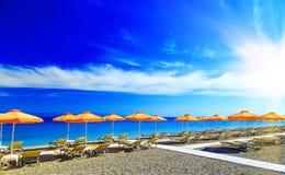 Griekenland, rietparaplu's en gele sunbeds op het kiezelsteenstrand bij Egeïsche Overzees van Rhodos, Griekenland Royalty-vrije Stock Fotografie