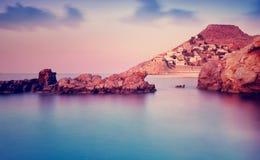 Grieks eiland in purpere zonsondergang Stock Afbeelding