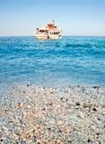 Grieks marmeren strand, blauwe overzees en cruiseboot stock foto