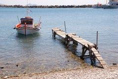 Griekse die vissersboot aan een rachitische oude pier wordt vastgelegd royalty-vrije stock afbeeldingen