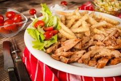 Griekse gyroscopen dis met gebraden gerechten en salade stock afbeelding