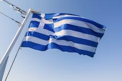 Griekse nationale vlag die op de wind tegen blauwe hemel golven Stock Foto