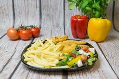 Griekse salade met kippenstrepen en frites stock afbeeldingen