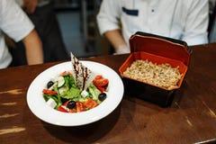 Griekse salade met olijven, tomaten, kaas en greens in een witte plaat en een rijst in een vakje tegen een houten lijst stock fotografie