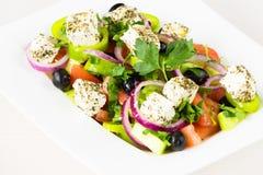 Griekse salade met verse tomaat, komkommer, rode ui, basilicum, feta-kaas, zwarte olijven, Italiaanse kruiden en olijfolie in wit Royalty-vrije Stock Foto's