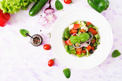 Griekse salade met verse tomaat, komkommer, rode ui, basilicum, sla, feta-kaas, zwarte olijven en Italiaanse kruiden Royalty-vrije Stock Afbeelding