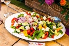 Griekse salade op een witte ovale plaat Stock Afbeelding