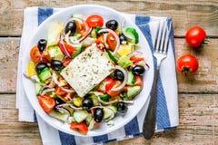Griekse salade van organische tomaten, komkommer, rode ui, olijven en feta-kaas Stock Afbeeldingen