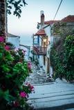 Griekse sidestreet dichtbij zonsondergang met bloemen stock foto