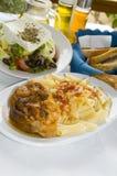 Griekse stifada van het voedsel klassieke kalfsvlees met knapperige br van de deegwaren Griekse salade stock foto