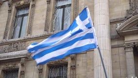 Griekse vlag die op de sterke wind op de achtergrond van gebouwen golven stock video