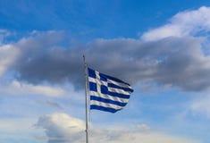 Griekse vlag die trots agains dramatische bewolkte blauwe hemel vliegen royalty-vrije stock foto's
