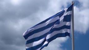 Griekse vlag die in wind tegen duidelijke blauwe hemel golven Griekse Vlag in Helder Zonlicht stock videobeelden