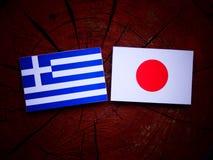 Griekse vlag met Japanse vlag op een geïsoleerde boomstomp royalty-vrije stock foto