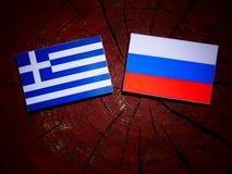 Griekse vlag met Russische vlag op een boomstomp stock fotografie