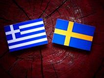 Griekse vlag met Zweedse vlag op een boomstomp stock foto