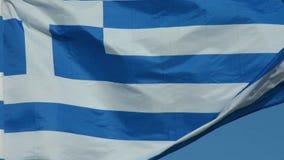 Griekse vlag op pool die over blauwe achtergrond golven stock videobeelden