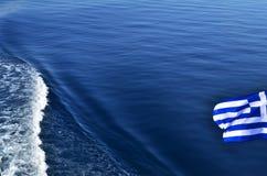 Griekse vlag over zeewaters Stock Afbeelding