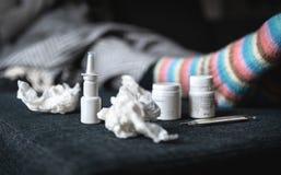 griep en koude geneeskunde Zieke vrouw met neusnevel, warme wollen sokken, weefsels en thermometer die op laag thuis rusten stock afbeeldingen