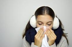 Griep of koude - het niezen vrouwen zieke blazende neus Jonge vrouw die koud dragend oorbeschermers, scraf en sweater zijn De rui stock afbeelding