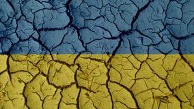 Grietas del fango con la bandera de Ucrania imágenes de archivo libres de regalías