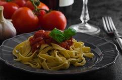 Grießteigwaren mit würziger Tomatensalsa, -knoblauch und -basilikum Stockbilder