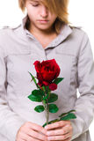 Grieve. A young woman with a red rose, obvious grieve but this photo could also be used for romance. Focus is on the rose Stock Images