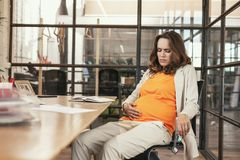 Grieved pregnant CEO having sickness. Discomfort of pregnancy. Sorrowful pregnant CEO sitting at table and looking at tummy stock image