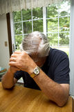 Grieving Man at Table Royalty Free Stock Images