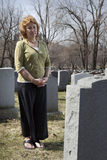 Grieving widow. In front of cemetery tombstone Stock Photography