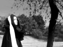 Grieving widow. Woman in black robe with a white scarf at sundown - widow walking away from the grave Stock Photos