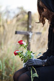 Grieving widow. Widow at the cemetary holdig red roses in her hands Royalty Free Stock Images